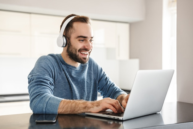 Freelancer feliz homem bonito sentado à mesa da cozinha, trabalhando em um computador laptop, usando headhones