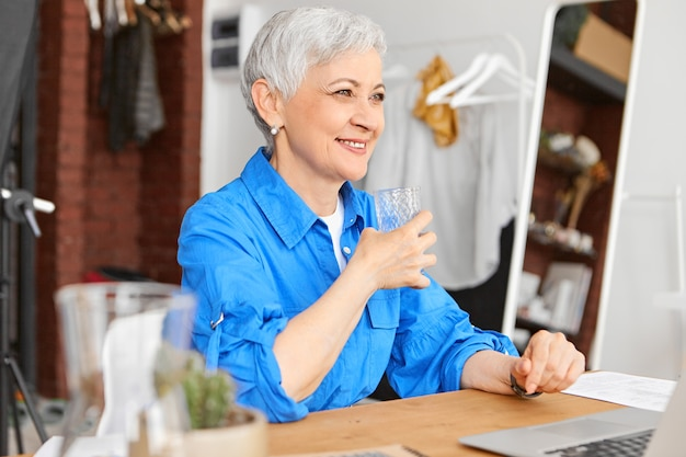 Freelancer fêmea madura atraente positiva desenvolvendo novos hábitos saudáveis, sentada em frente a um computador portátil aberto, segurando um copo de água, refrescando-se durante um pequeno intervalo, sorrindo alegremente
