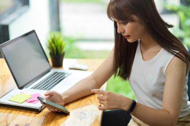 Freelancer feminina paga despesas mensais via aplicativo de pagamento online em smartphone retém cartão de crédito Foto Premium