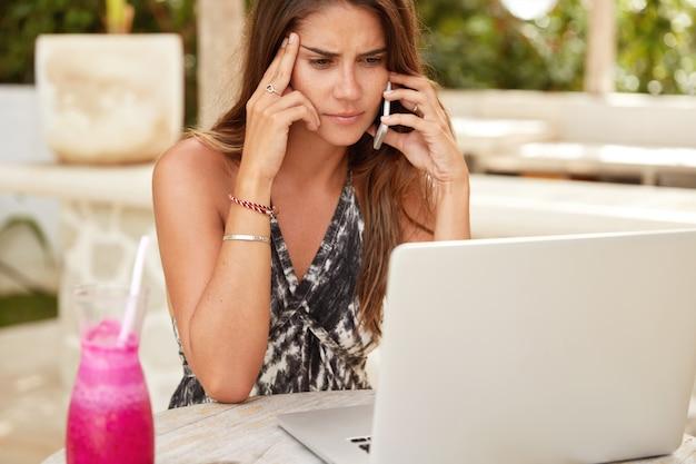 Freelancer feminina séria tenta resolver algum problema, conversa com o chefe via celular, focada na tela do laptop, rodeada de coquetel fresco, trabalha remotamente durante o descanso no resort
