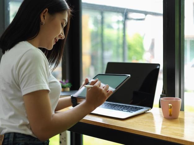 Freelancer feminina trabalhando com simulação de tablet e laptop no bar do café