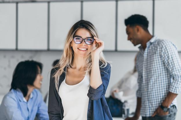 Freelancer feminino caucasiano elegante em camisa preta, posando no novo escritório, enquanto seus colegas conversando. retrato interno de estudante animado em copos se divertindo após exames difíceis com amigos.