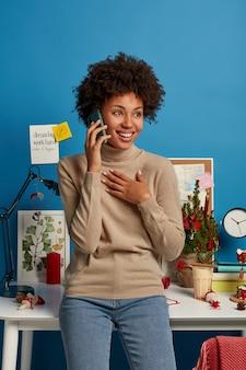 Freelancer feminino de cabelos cacheados alegre tem uma discussão com um colega de trabalho, gosta de conversa ao telefone, fica feliz em ouvir algo, sente-se feliz com o trabalho remoto, fica no próprio armário perto do local de trabalho.