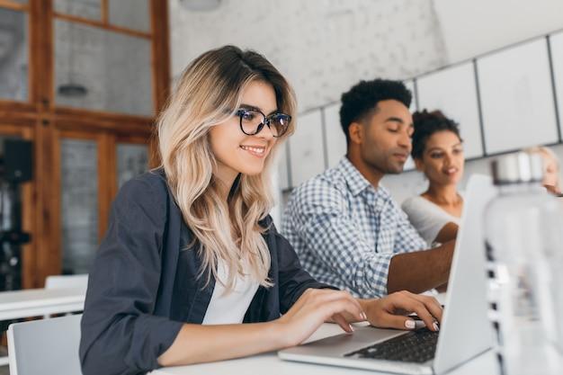 Freelancer feminino encaracolado lindo com manicure bonita usando laptop e sorrindo. retrato interior da secretária loira sentada ao lado de um colega de trabalho africano de camisa azul.