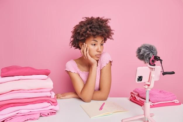 Freelancer feminino encaracolado sério e atencioso assiste ao vídeo como lavar a roupa em casa, senta-se à mesa com a roupa dobrada isolada sobre o rosa