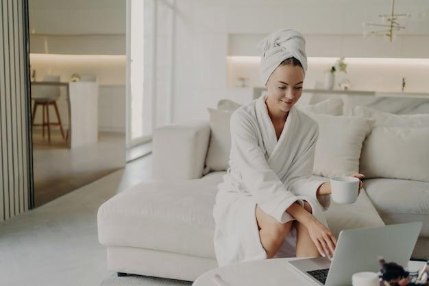 Freelancer feminino jovem relaxado em roupão branco e toalha na cabeça, bebendo café ou chá e trabalhando remotamente em um computador laptop, descansando no sofá na moderna sala de estar depois de tomar banho