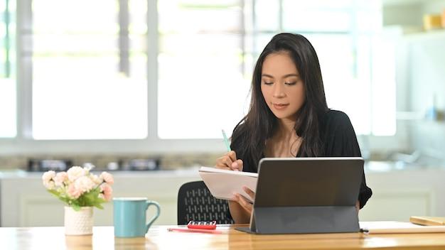Freelancer feminino jovem tomando nota e trabalhando com tablet no escritório em casa.