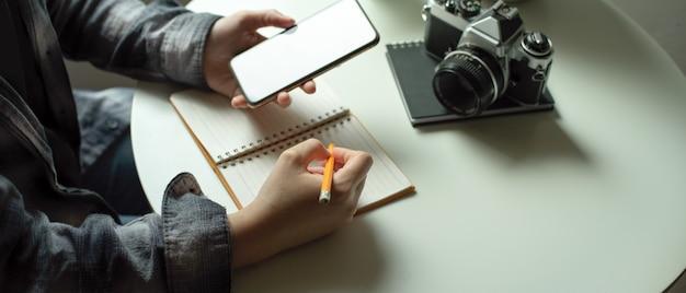 Freelancer feminino, observando no livro de agenda enquanto procurava informações no smartphone mock-up