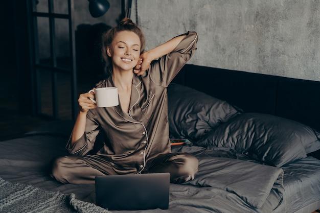 Freelancer feminino relaxado tomando uma xícara de café stright depois de acordar na cama enquanto verifica novas mensagens e e-mails no laptop, vestido de pijama. mulher de olhos fechados pronta para iniciar trabalho remoto