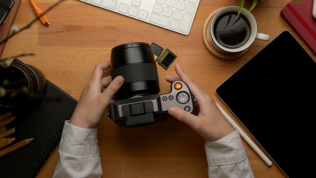 Freelancer feminino segurando a câmera digital na mesa de trabalho de madeira com tablet digital e suprimentos