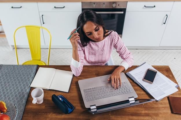 Freelancer feminino trabalhar no computador portátil em casa. vista do topo.