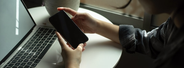 Freelancer feminino usando smartphone enquanto trabalhava com o laptop na mesa de círculo branco ao lado da janela