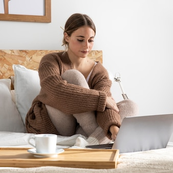 Freelancer full shot trabalhando na cama