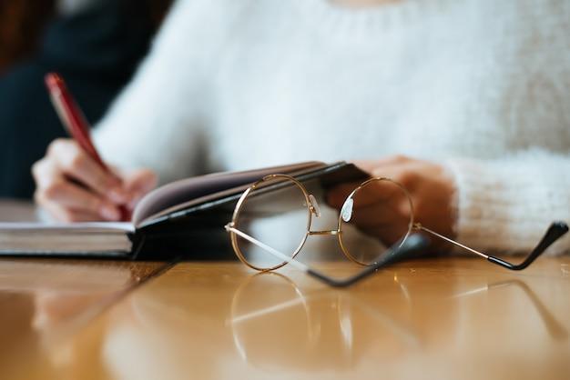 Freelancer garota com uma jaqueta branca trabalha, escreve em um caderno, em um café