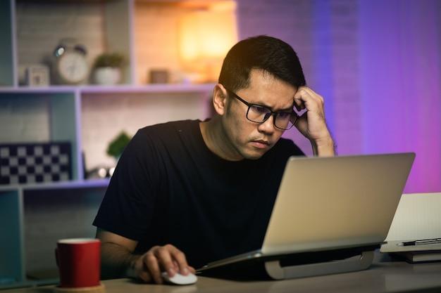 Freelancer homem sério e ocupado trabalhando com o laptop em cima da mesa, conceito de trabalho em casa