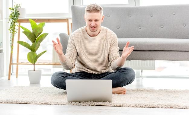 Freelancer homem trabalhando em casa com laptop e surpreso levantando as mãos