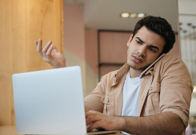 Freelancer indiano usando laptop, internet, falando no celular, comunicação, trabalhando em casa