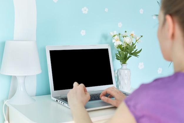 Freelancer irreconhecível jovem trabalha remotamente em casa, senta-se no interior azul doméstico acolhedor na frente do computador portátil moderno aberto com tela de cópia em branco para o seu texto promocional