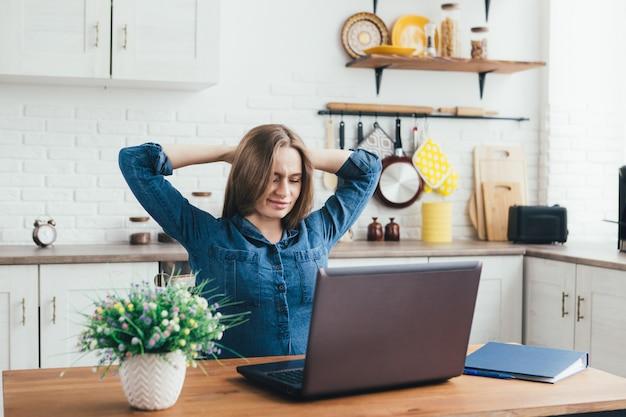 Freelancer jovem, bonita e grávida, trabalha em casa na cozinha em modo de auto-isolamento em quarentena e faz um aquecimento de fadiga