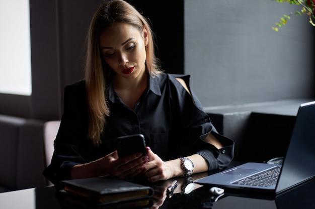 Freelancer jovem elegante encantadora vestindo camisa preta e trabalhando no telefone no local de trabalho