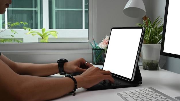 Freelancer jovem está digitando no tablet do computador com tela em branco enquanto está sentado no escritório.