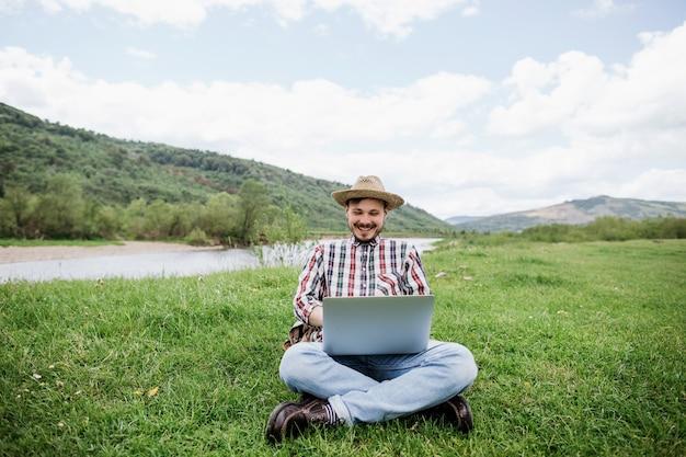Freelancer jovem feliz caucasiano trabalhando em seu laptop ao ar livre nas montanhas