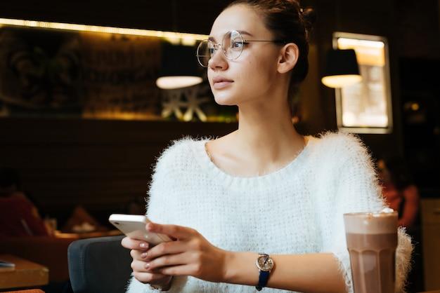 Freelancer linda jovem de óculos sentada em um café, segurando um smartphone, na mesa está um delicioso cappuccino