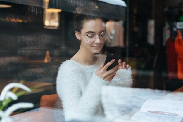 Freelancer linda jovem de suéter branco e óculos escreve uma mensagem no smartphone, em um café
