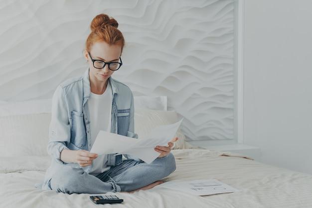 Freelancer linda mulher ruiva olha atentamente para documentos, calcula, administra finanças