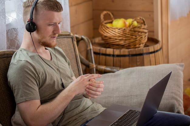 Freelancer masculino bonito se comunicando em rede social e trabalhando remotamente de casa