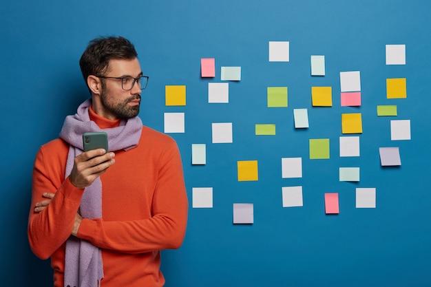 Freelancer masculino com barba por fazer olha de lado, trabalha no escritório, usa um gadget moderno para verificar o feed de notícias, usa cachecol e suéter
