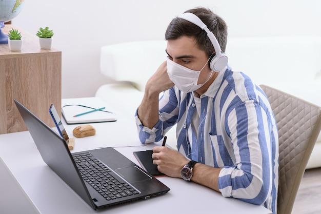 Freelancer masculino com camisa listrada e máscara médica no rosto sentado trabalhando no laptop