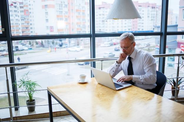 Freelancer masculino está trabalhando em um café em um novo projeto de negócios. senta-se em uma grande janela na mesa. olha para a tela de um laptop com uma xícara de café