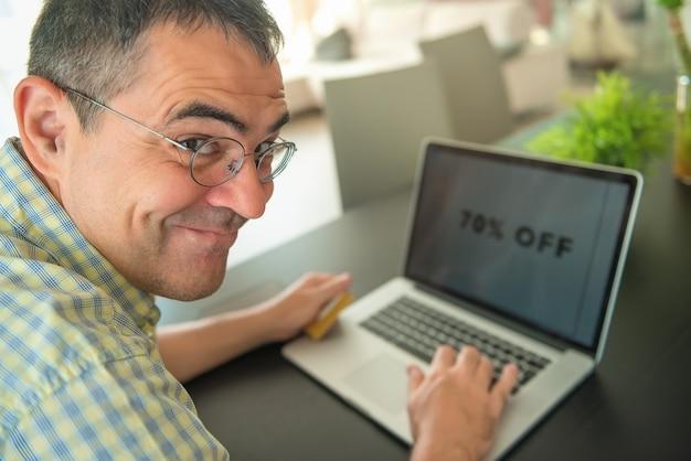 Freelancer masculino maduro caucasiano de sorriso que trabalha em um portátil em casa, 70% fora no portátil.