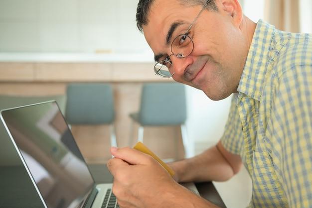Freelancer masculino maduro caucasiano que trabalha em um portátil em casa.