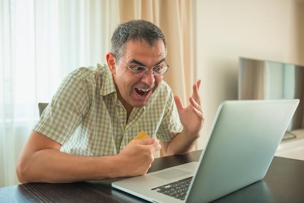 Freelancer masculino maduro que trabalha em um portátil em casa. sucesso e felicidade, conceito de venda.