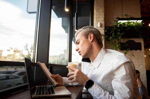 Freelancer masculino ocupado olha o diário, acerta o prazo com o cliente e bebe um café com leite