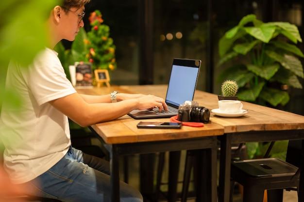 Freelancer masculino que trabalha no portátil em tardio na cafetaria.