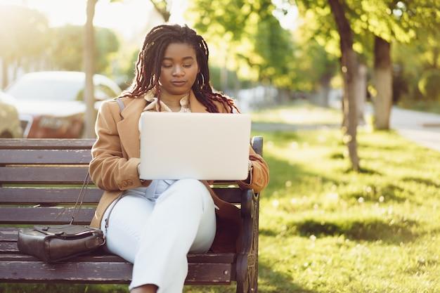 Freelancer mulher sentada em um banco em uma rua e usando laptop