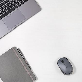 Freelancer no local de trabalho. portátil moderno cinzento, pena metálica, caderno e rato do computador no fundo claro com espaço da cópia. vista do topo. lay plana.