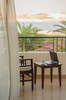 Freelancer ou empresário trabalhando remotamente com o laptop na varanda do hotel no resort durante a viagem. local de trabalho sem pessoas
