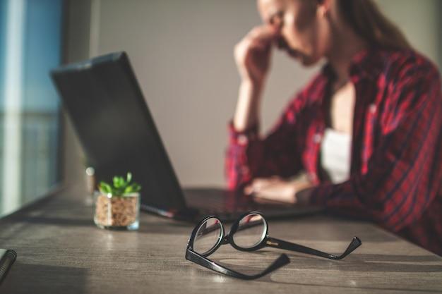 Freelancer sentindo cansaço visual após um longo dia de trabalho e usando um laptop.