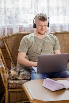 Freelancer sorridente e bonito trabalhando remotamente de casa usando um laptop