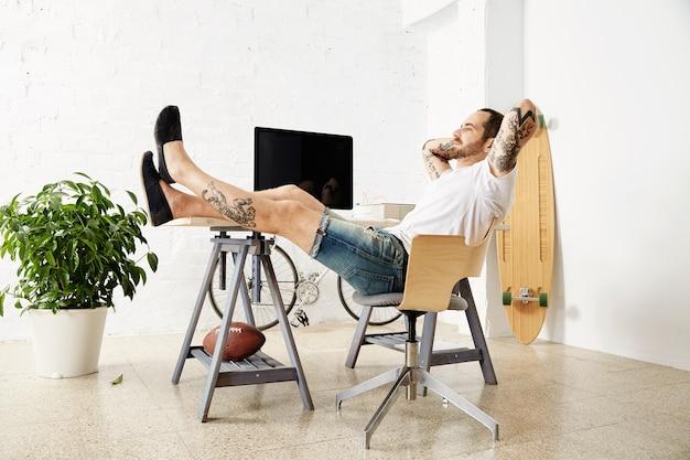 Freelancer tatuado e relaxante, sonhadoramente olhando pela janela, enquanto faz uma pausa no trabalho, com as pernas na mesa dentro de um grande loft branco