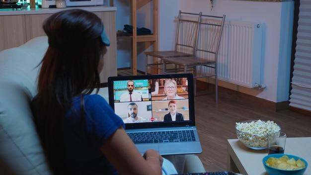 Freelancer, tendo uma conversa virtual com colegas no laptop, sentado no sofá de pijama. trabalhador remoto discutindo durante reunião on-line, consultando a equipe em videochamada usando tecnologia de internet