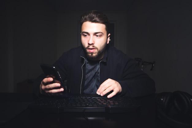 Freelancer, trabalha em casa no computador e olha para a tela do telefone