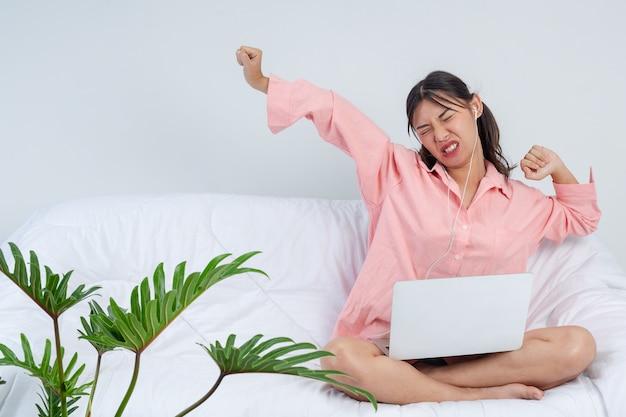 Freelancer, trabalhando em casa - a jovem mulher está esticando depois de terminar o trabalho no sofá, ela está ouvindo música.