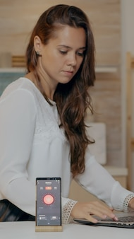 Freelancer, trabalhando em casa com sistema de iluminação de automação, sentado na cozinha, acendendo as luzes usando o comando de voz para o aplicativo de casa inteligente no smartphone. pessoa monitorando luz com dispositivo wi-fi