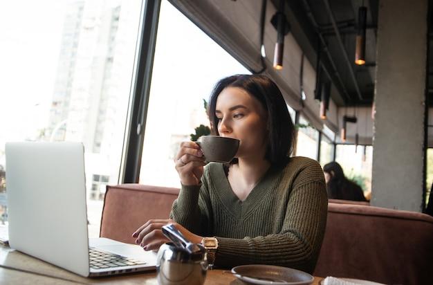 Freelancer, trabalhando no conceito de ambiente aconchegante. jovem concentrada bebe café em xícara cinza