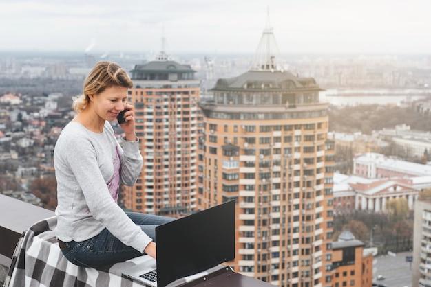 Freelancer trabalhando no telhado de um arranha-céu